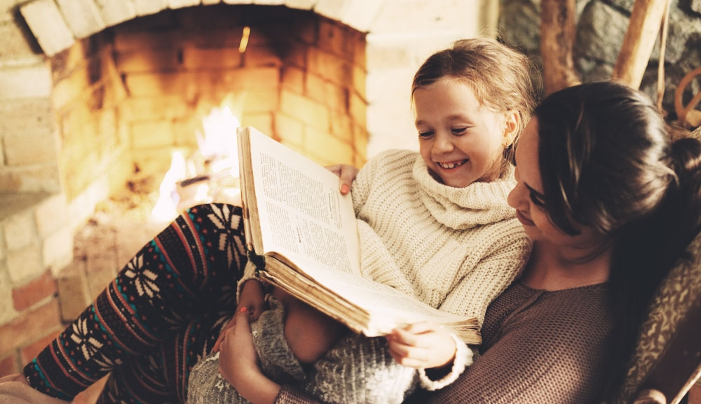 A child sits on her mothers lap and reads a storybook by the fire