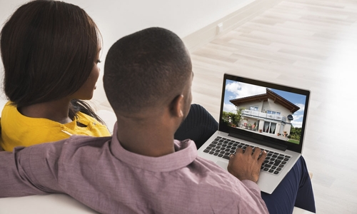 A couple browse house listings on a laptop