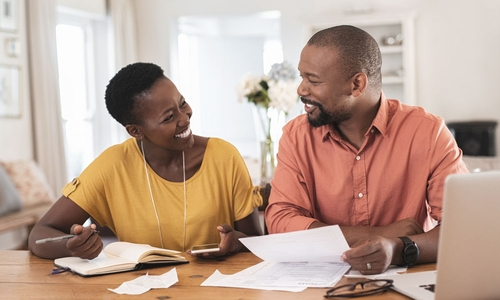 A happy man and woman review their finances together