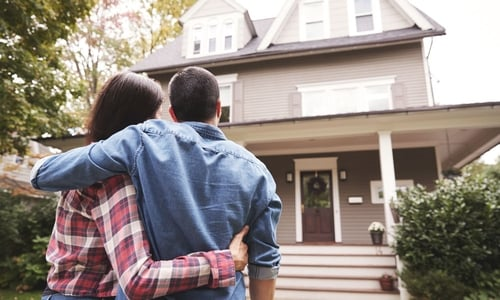 A man and woman embrace as they stand looking up at their house