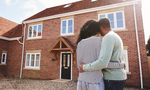 A man and woman embrace in front of their brick house