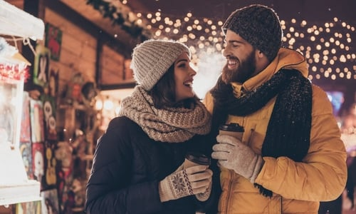 A man and woman in winter attire hold hot drinks and walk through a holiday market