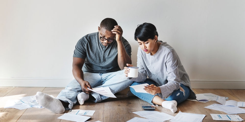 A man and woman look concerned at paperwork as they sit on the floor
