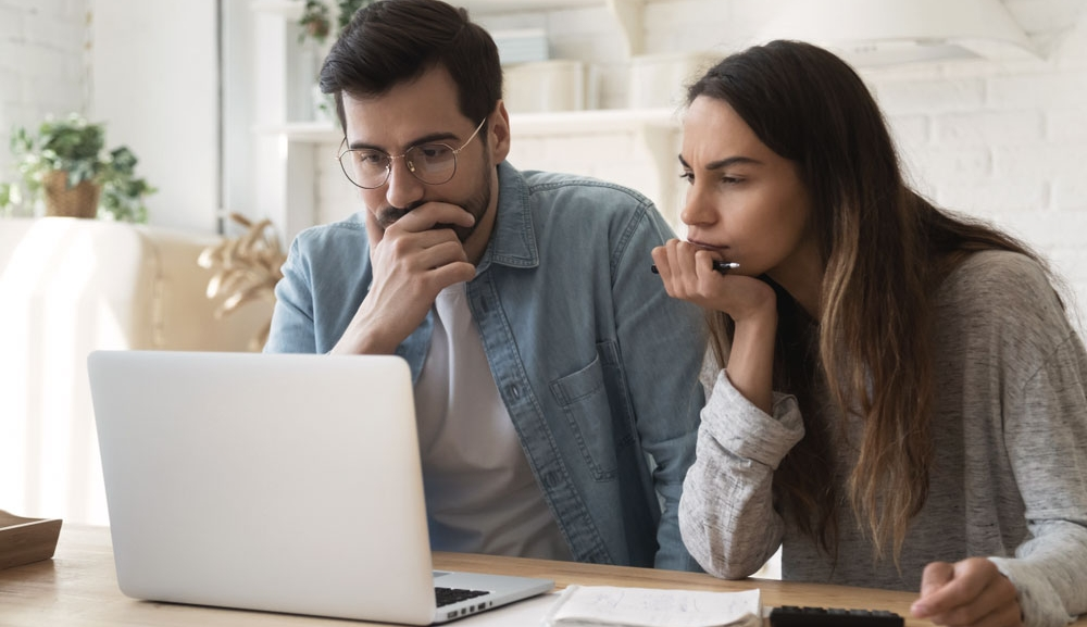 A man and woman look worried at the computer