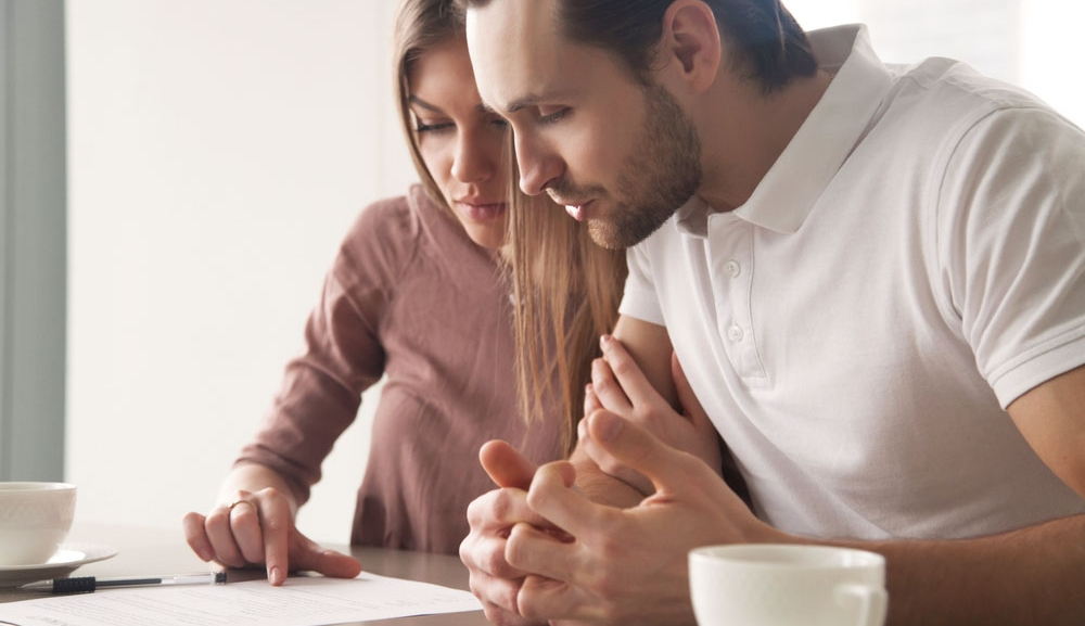 A man and woman looked concerned at paperwork as they sit at a table