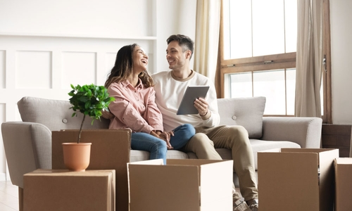 A man and woman sit on a couch with moving boxes on the floor