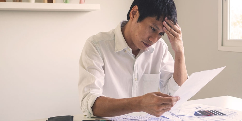 A man looks concerned as he reviews his bills and statements