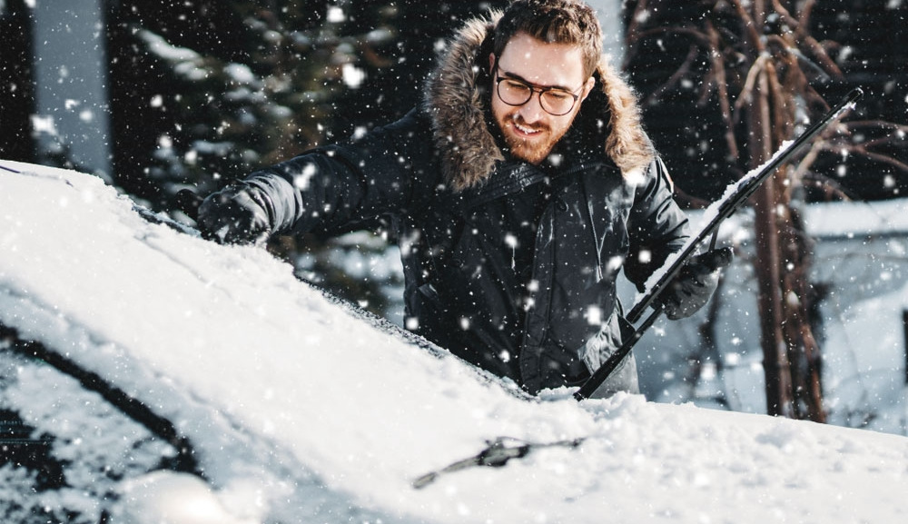 A man with glasses brushes the snow off his car