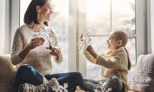 A mother and child cut out paper snowflakes by the window
