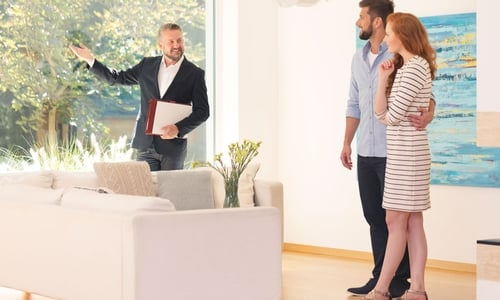 A realtor shows a house to a young couple