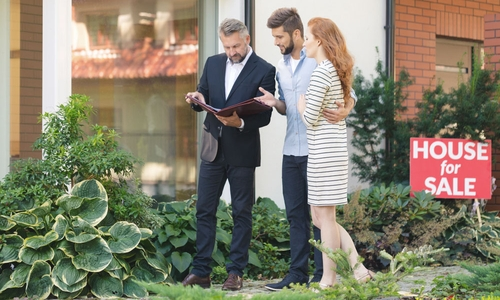 A realtor shows a listing to a young couple who are house hunting
