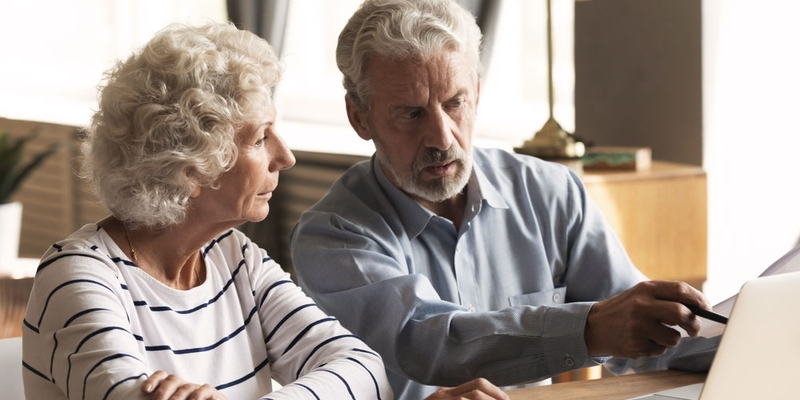 A senior woman sits next to a senior man and points at a computer with a worried look on his face