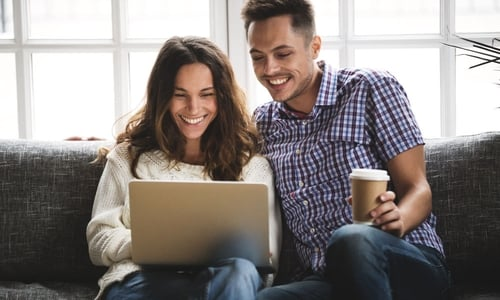 A smiling man holding a coffee sits next to a happy woman holding a laptop