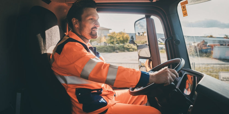 A truck driver sits behind the wheel in a neon orange outfit
