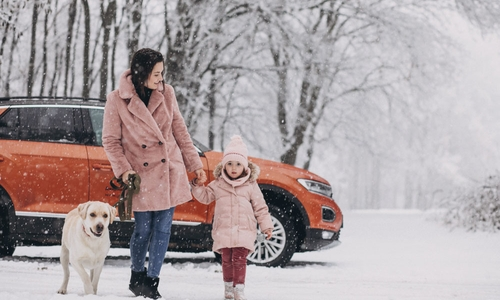 A woman dog and child walk by an orange SUV in the snow