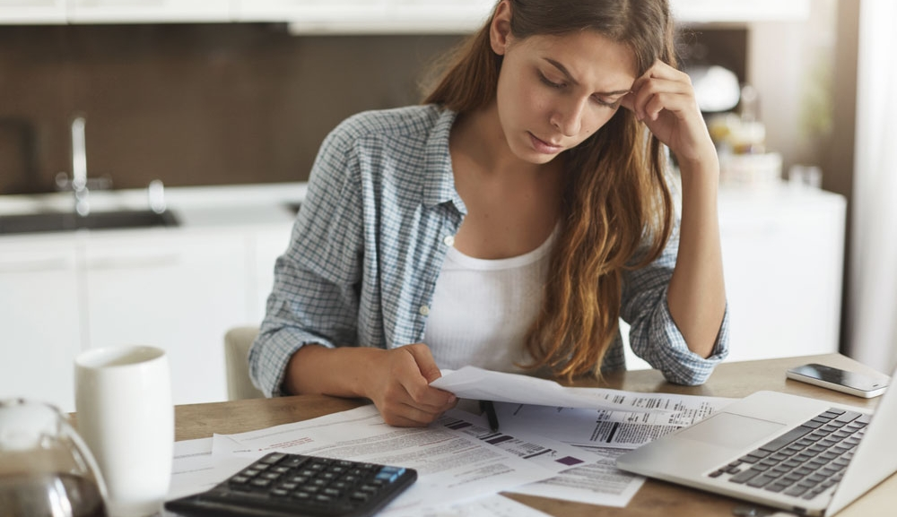 A woman looks concerned as she checks her bills and statements