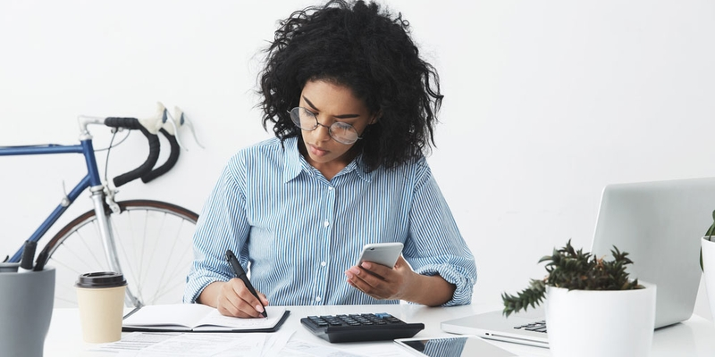 A woman tracks her finances with a notebook and phone