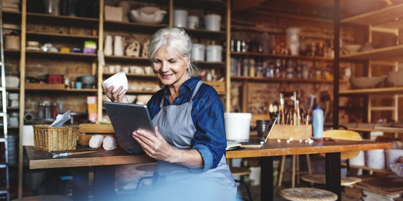 A woman wearing overalls holds pottery and looks at a tablet