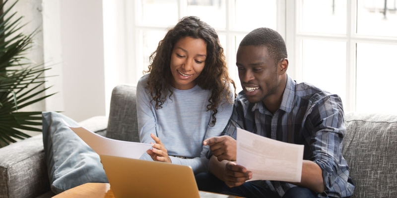 A young couple happily look at documents and a laptop computer