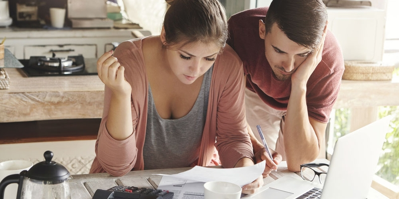 A young couple look distressed at paperwork