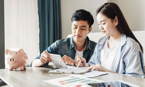 A young couple sit at a table with a piggy bank, paperwork and calculator