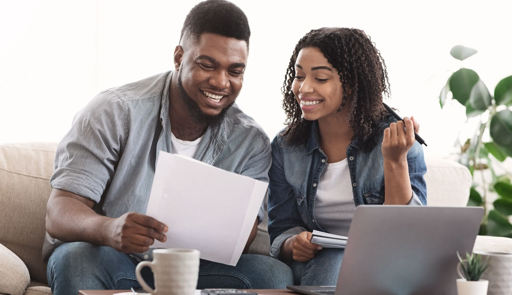 A young couple smile as they look at documents