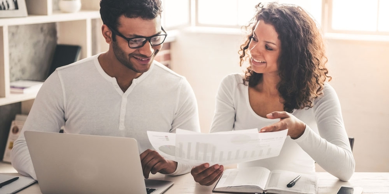 A young man and woman look at their finances and smile happily