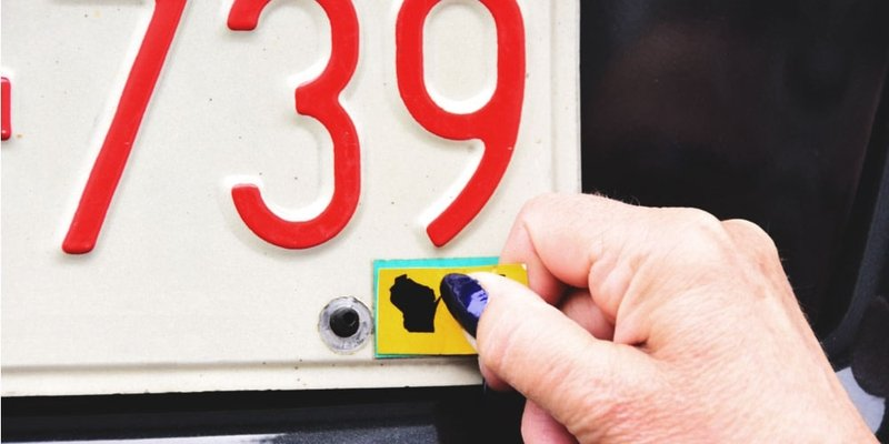 A hand removes an Alberta licence plate sticker