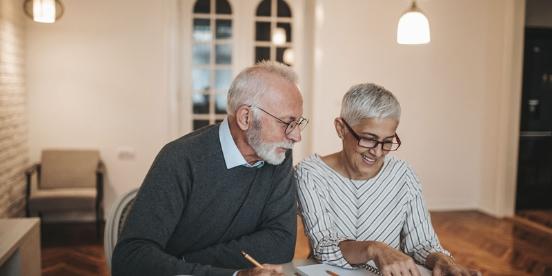 An older couple track their finances with a calculator