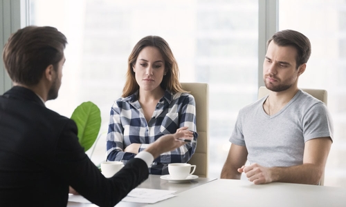 An unhappy couple sit talking with a broker in an office