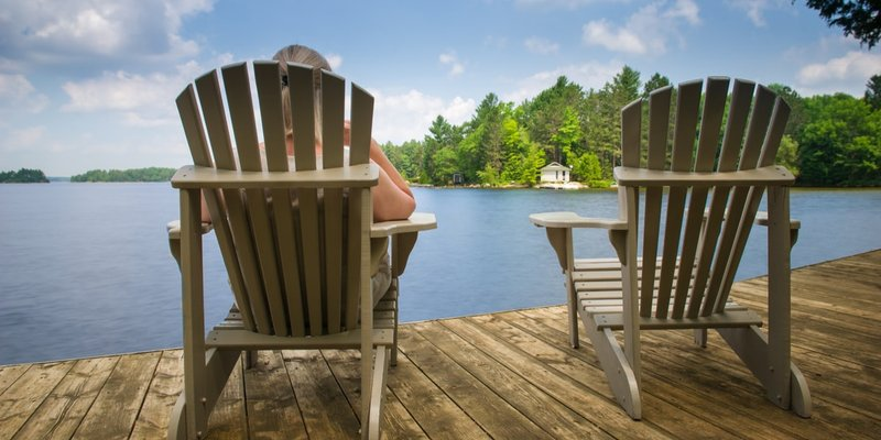 A person sitting on a dock enjoying the view at their cottage.