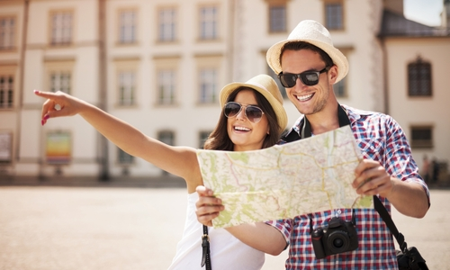 Couple travelling wearing sunglasses and holding map