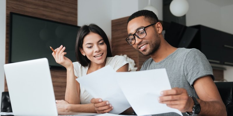 Young couple reviewing documents in front of computer