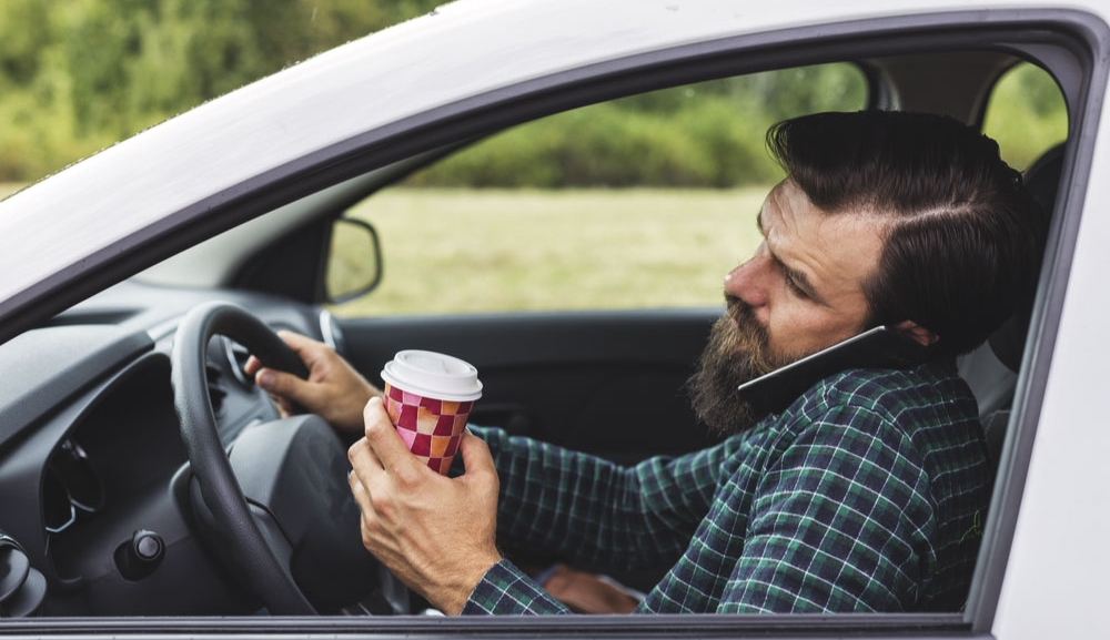 A driver holds a cellphone to hear ear with his shoulder and a coffee cup in one hand and the wheel of his car in the other