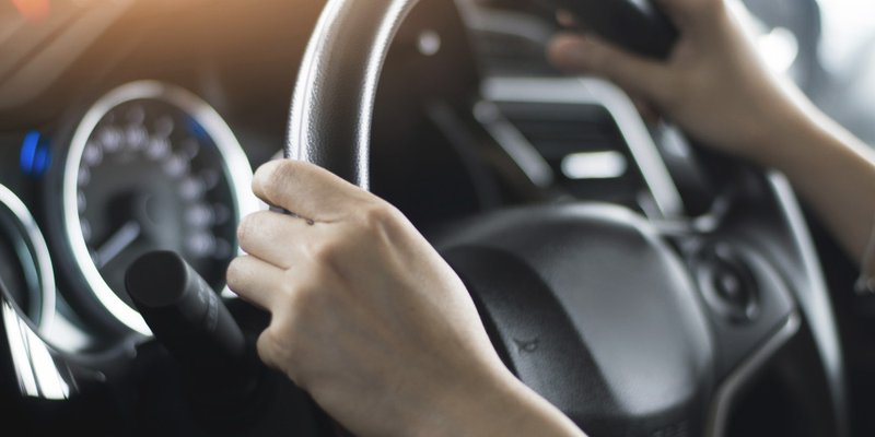 A close-up image of hands on a steering wheel