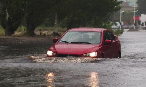 A red car drives through flood waters