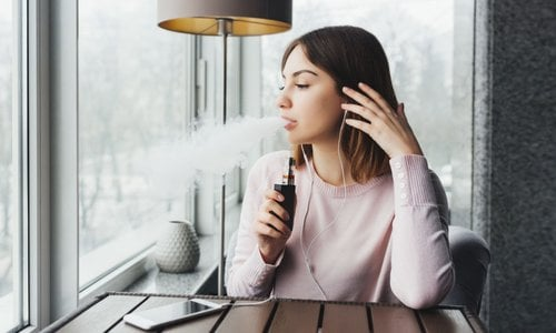A young woman sits vaping indoors while listening to music on her smartphone