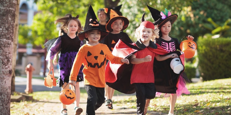 A group of kids run down the street in Halloween costumes