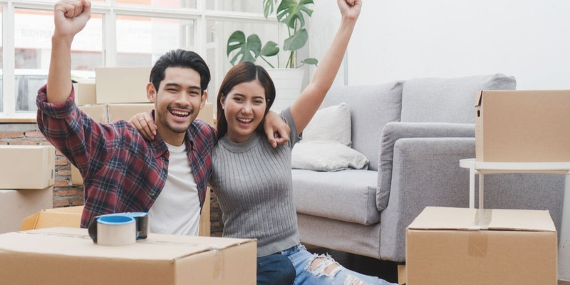 A happy couple sit amongst boxes in their new apartment
