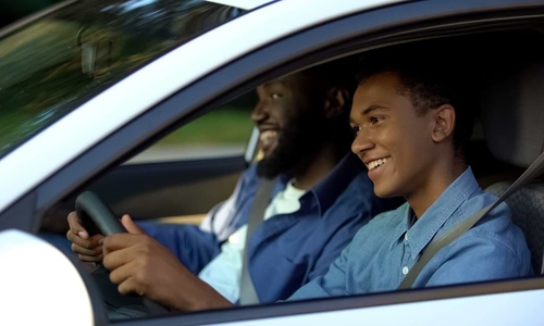 Happy african-american father and teen sitting in car, dad pleased with sons drive