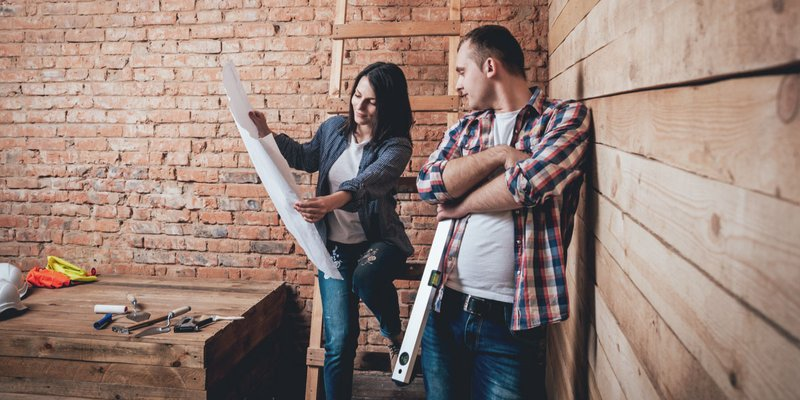 A woman holds blueprints open to show a man during a home renovation