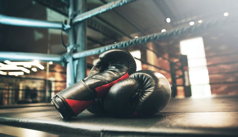 Boxing gloves resting on the edge of a boxing ring