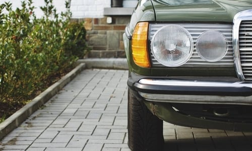 An older green car sits parked in a driveway