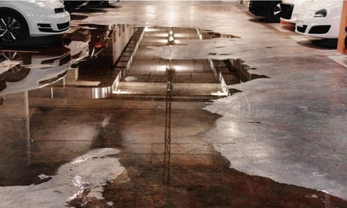 Water covers the floor of a parking garage