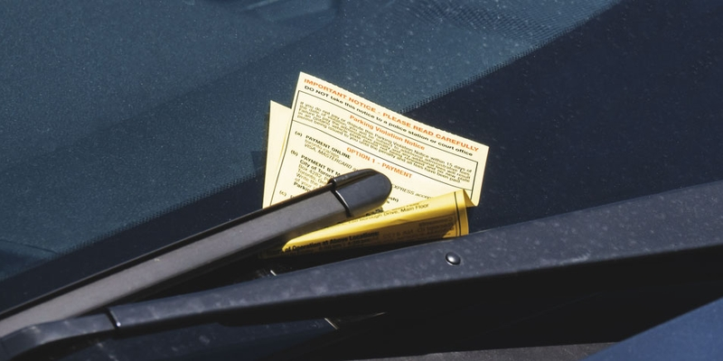 A parking ticket is tucked under a windshield wiper