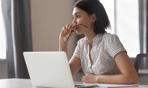 A young woman sits at her computer staring off in deep thought