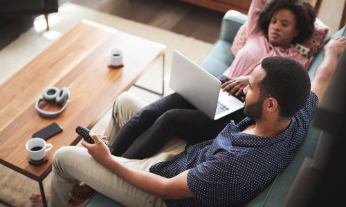 Overhead shot of a couple relaxing at home on their couch. The man is watching tv and the woman is surfing on her laptop.