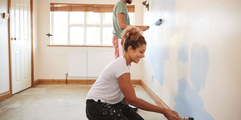 A couple paints the bedroom walls of their new apartment blue