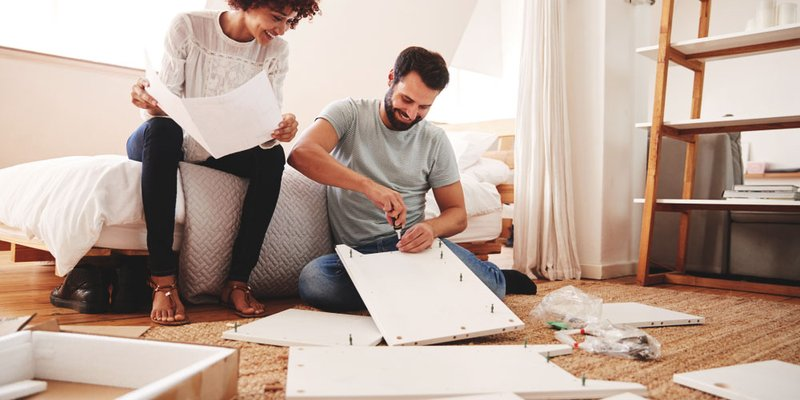 A couple builds ikea furniture together in their new home