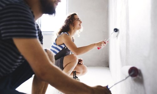 A couple paints their new apartment walls white